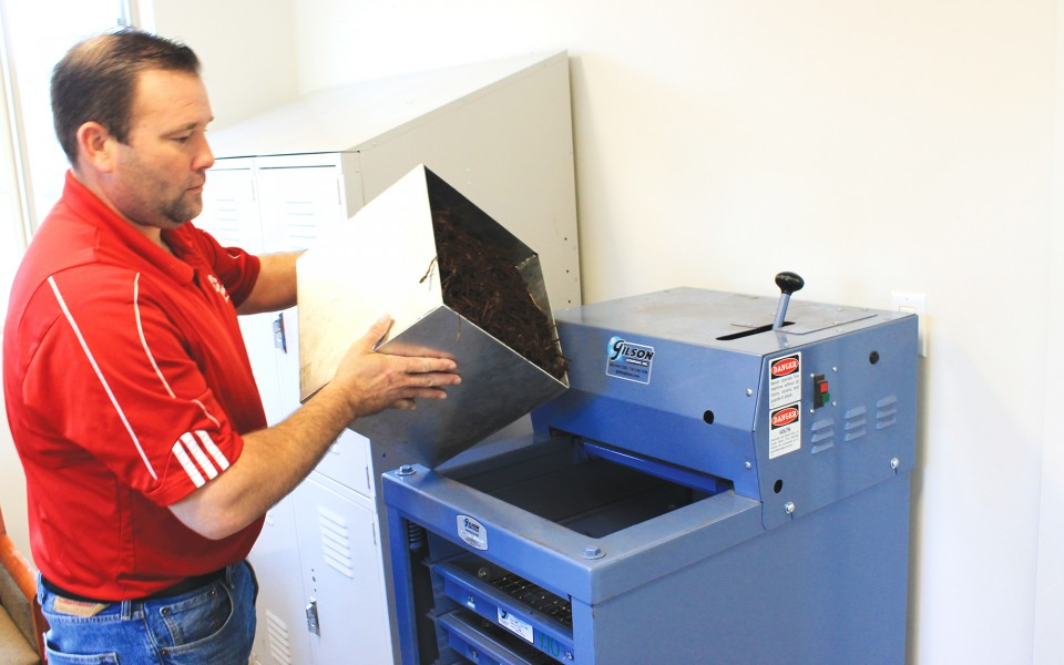 Hughes Mulch employee using quality control equipment
